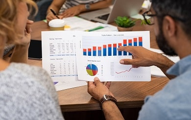 Mature latin businessman showing stock market bar graph to businesswoman. Financial advising team discussing trading patterns of year. Rear view of casual businesspeople holding charts studying year trend together.